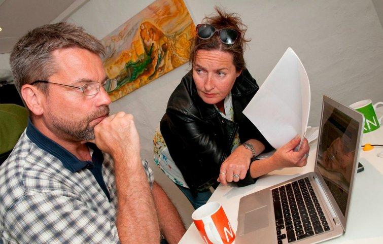 Et par sidder foran pc og med papir i hånden og diskuterer deres boligøkonomi